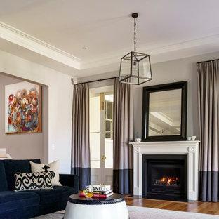 シドニーの大きいトラディショナルスタイルのおしゃれな独立型リビング (青い壁、無垢フローリング、標準型暖炉、木材の暖炉まわり、茶色い床) の写真