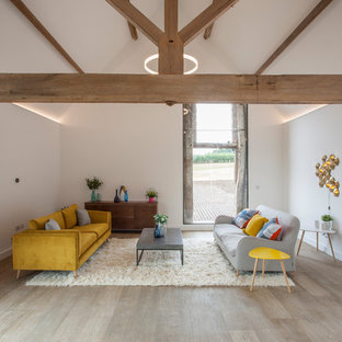Farmhouse living room in West Midlands with white walls, light hardwood flooring and beige floors.