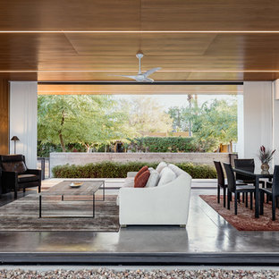This is an example of a medium sized modern open plan living room in Phoenix with concrete flooring, a wall mounted tv, brown walls, no fireplace and grey floors.
