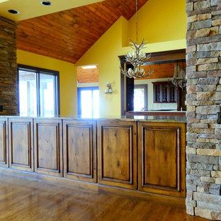 シャーロットの巨大なラスティックスタイルのおしゃれなLDK (黄色い壁、無垢フローリング、標準型暖炉、石材の暖炉まわり、壁掛け型テレビ) の写真