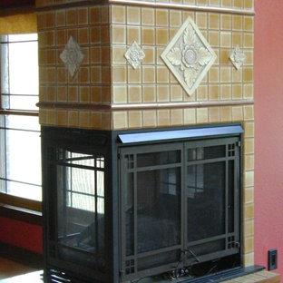 Idee per un soggiorno stile americano aperto con pareti rosse, camino bifacciale e cornice del camino piastrellata