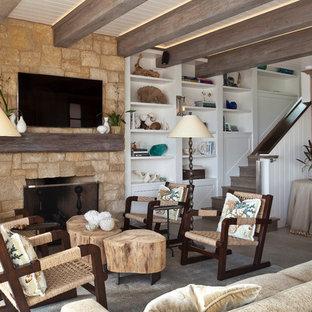 オレンジカウンティの中サイズのビーチスタイルのおしゃれなLDK (フォーマル、白い壁、標準型暖炉、石材の暖炉まわり、壁掛け型テレビ、ライムストーンの床、ベージュの床) の写真