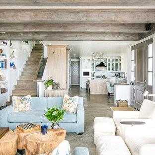オレンジカウンティの中くらいのビーチスタイルのおしゃれなリビング (白い壁、ライムストーンの床、標準型暖炉、石材の暖炉まわり、壁掛け型テレビ、ベージュの床) の写真