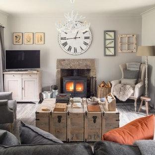 Small cottage enclosed gray floor living room photo in Other with white walls, a tv stand, a wood stove and a metal fireplace