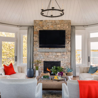 ボストンのビーチスタイルのおしゃれなリビング (グレーの壁、無垢フローリング、標準型暖炉、石材の暖炉まわり、壁掛け型テレビ、塗装板張りの天井) の写真