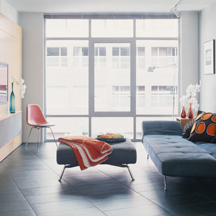 This is an example of a small modern open concept living room in Los Angeles with a built-in media wall, grey walls and ceramic floors.