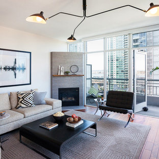 Mid-sized trendy formal and open concept medium tone wood floor living room photo in San Diego with white walls, a corner fireplace and a metal fireplace