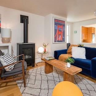 Foto di un piccolo soggiorno minimal chiuso con pareti bianche, parquet chiaro, stufa a legna, TV nascosta e pavimento marrone