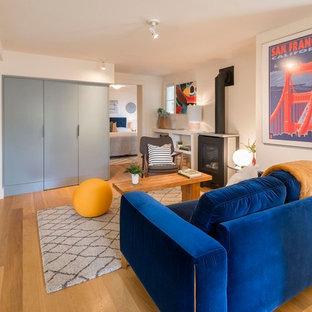 Ejemplo de salón cerrado, moderno, pequeño, con paredes blancas, suelo de madera clara, estufa de leña, televisor retractable y suelo marrón