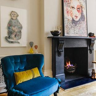 Ejemplo de salón para visitas clásico con suelo de madera clara, todas las chimeneas, marco de chimenea de hormigón y paredes beige