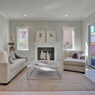 Imagen de salón para visitas abierto, clásico renovado, de tamaño medio, sin televisor, con chimenea tradicional, marco de chimenea de piedra, suelo de madera clara y paredes grises
