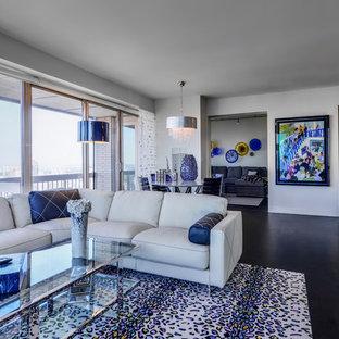 Foto på ett mellanstort funkis allrum med öppen planlösning, med vita väggar, ett finrum, betonggolv, en väggmonterad TV och svart golv