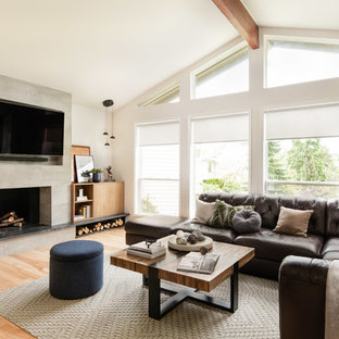 Inspiration for a mid-sized contemporary open concept light wood floor and beige floor living room remodel in Seattle with white walls, a standard fireplace, a wall-mounted tv and a concrete fireplace