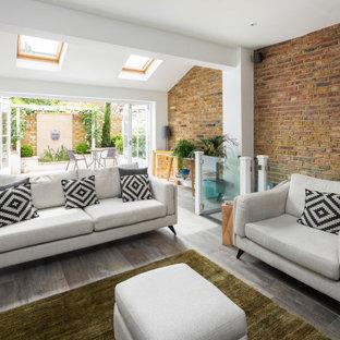Aménagement d'un salon contemporain ouvert avec un mur rouge, un sol en bois foncé, un sol marron et un mur en parement de brique.
