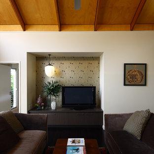 Foto på ett mellanstort funkis vardagsrum, med vita väggar, en fristående TV och mörkt trägolv