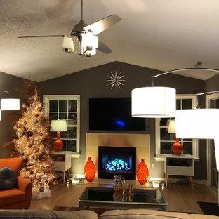Foto di un grande soggiorno minimalista con pareti grigie, pavimento in laminato, camino classico, cornice del camino in pietra e TV a parete