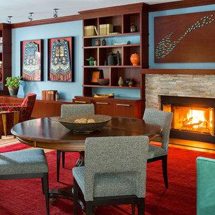 Immagine di un grande soggiorno chic aperto con pareti blu, pavimento in legno massello medio, camino classico, cornice del camino in pietra e parete attrezzata