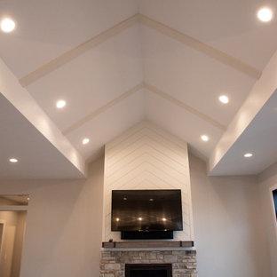 Ejemplo de salón abierto y abovedado, minimalista, grande, con paredes grises, suelo vinílico, chimenea tradicional, televisor colgado en la pared y suelo marrón