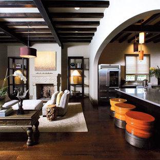Diseño de salón abierto, mediterráneo, con suelo de madera oscura y chimenea tradicional