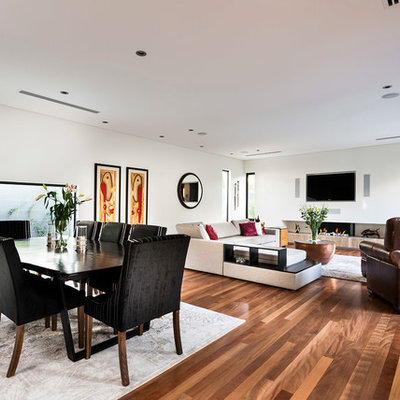 Example of a large trendy open concept medium tone wood floor living room design in Perth with white walls, a ribbon fireplace and a wall-mounted tv