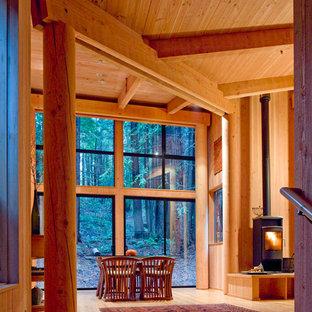 Modelo de salón abierto, moderno, pequeño, con suelo de madera clara, estufa de leña y marco de chimenea de baldosas y/o azulejos