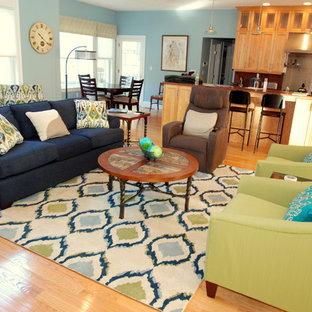 Foto di un ampio soggiorno classico aperto con pareti blu, parquet chiaro, camino classico, cornice del camino in pietra e TV a parete