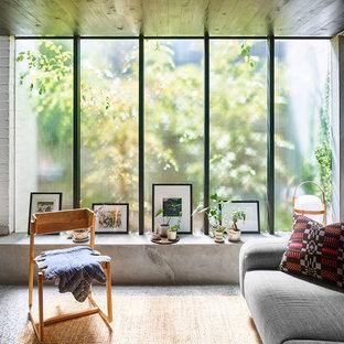 Foto di un soggiorno minimalista di medie dimensioni e aperto con pareti grigie, pavimento in cemento, stufa a legna, cornice del camino in mattoni, TV nascosta e pavimento grigio