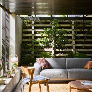 Modelo de salón abierto, minimalista, de tamaño medio, con suelo de cemento, estufa de leña, marco de chimenea de ladrillo, televisor retractable, suelo gris y paredes grises