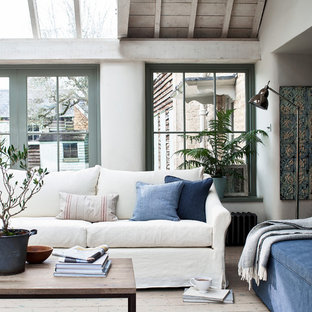 Inspiration for a mediterranean living room in Wiltshire with white walls, light hardwood flooring and beige floors.