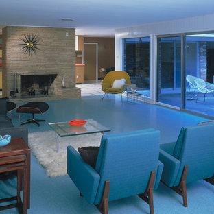 Foto de salón moderno con marco de chimenea de piedra y suelo azul
