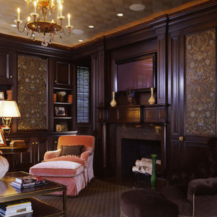 Example of a classic living room library design in Boston with brown walls