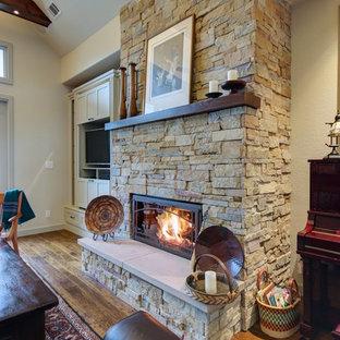 Exemple d'un salon craftsman de taille moyenne et ouvert avec un mur beige, un sol en bois brun, une cheminée standard, un manteau de cheminée en pierre et un téléviseur encastré.