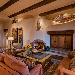 Offenes Mediterranes Wohnzimmer mit beiger Wandfarbe, Eckkamin, verstecktem TV, braunem Holzboden und verputztem Kaminsims in Phoenix
