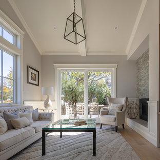 Diseño de biblioteca en casa cerrada, de estilo de casa de campo, pequeña, con paredes grises, suelo de madera clara, chimenea de doble cara, marco de chimenea de piedra, televisor colgado en la pared y suelo gris