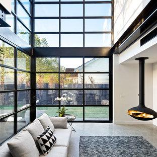 Immagine di un soggiorno contemporaneo di medie dimensioni e stile loft con pareti bianche, pavimento in cemento, camino sospeso e TV autoportante