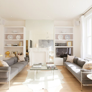 This is an example of a contemporary living room in London with white walls, light hardwood flooring and a built-in media unit.