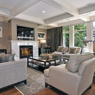 Idee per un soggiorno chic con cornice del camino in pietra, pareti beige, pavimento in legno massello medio, TV a parete e pavimento marrone