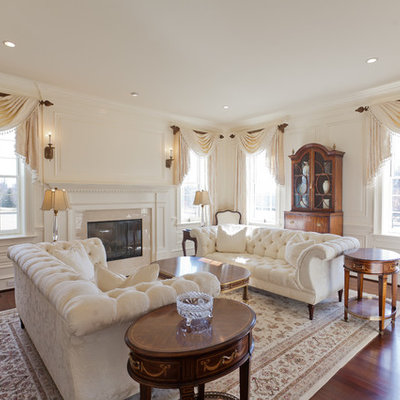 Example of a classic formal living room design in Philadelphia with beige walls and a standard fireplace