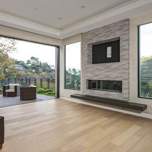 Exempel på ett mycket stort modernt allrum med öppen planlösning, med beige väggar, ljust trägolv, en bred öppen spis, en spiselkrans i gips, en inbyggd mediavägg och brunt golv