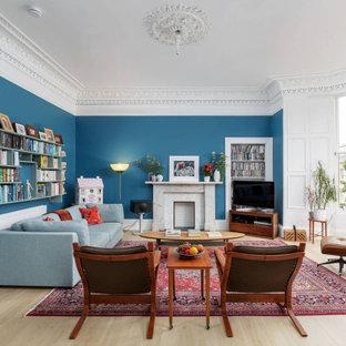 Klassisk inredning av ett allrum med öppen planlösning, med blå väggar, en standard öppen spis, en spiselkrans i sten, ljust trägolv, en fristående TV och beiget golv