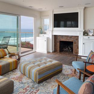 サンディエゴの中サイズのビーチスタイルのおしゃれなLDK (ベージュの壁、標準型暖炉、タイルの暖炉まわり、壁掛け型テレビ) の写真