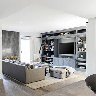 ロサンゼルスの大きいトランジショナルスタイルのおしゃれなLDK (ミュージックルーム、白い壁、無垢フローリング、標準型暖炉、タイルの暖炉まわり、埋込式メディアウォール) の写真