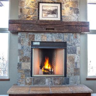 デンバーの大きいトラディショナルスタイルのおしゃれな独立型リビング (ライブラリー、緑の壁、無垢フローリング、標準型暖炉、石材の暖炉まわり、壁掛け型テレビ、黄色い床) の写真