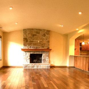 Foto de salón para visitas abierto, de estilo americano, pequeño, con paredes beige, suelo de madera oscura, chimenea tradicional, marco de chimenea de piedra, televisor colgado en la pared y suelo marrón