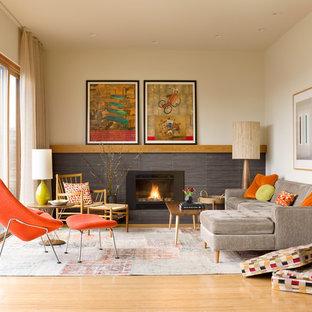 Fernseherloses, Offenes Retro Wohnzimmer mit hellem Holzboden, gefliester Kaminumrandung, Kamin und beiger Wandfarbe in Seattle