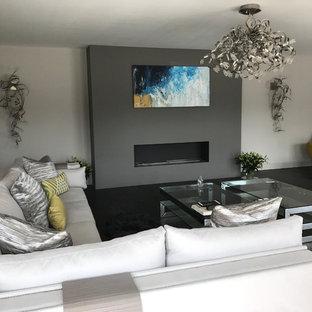 ロンドンの広いトラディショナルスタイルのおしゃれなリビング (壁掛け型テレビ、グレーの壁、濃色無垢フローリング、吊り下げ式暖炉、漆喰の暖炉まわり) の写真