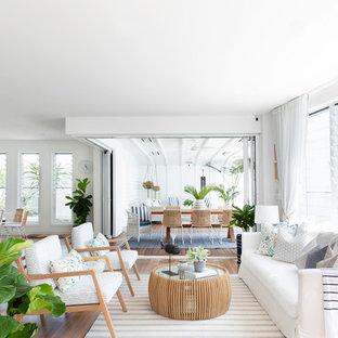 Ispirazione per un ampio soggiorno costiero aperto con pareti bianche, pavimento marrone, pavimento in vinile e nessuna TV