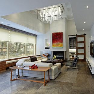 Modelo de salón abierto, actual, grande, con suelo de cemento, paredes blancas, chimenea tradicional, marco de chimenea de hormigón y pared multimedia