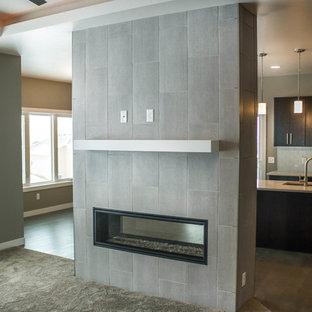 Idee per un soggiorno di medie dimensioni e aperto con sala formale, pareti grigie, pavimento in legno verniciato, camino bifacciale, cornice del camino piastrellata e TV a parete