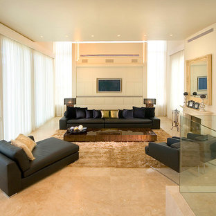 Example of a huge minimalist marble floor living room design in Other with beige walls, a standard fireplace and a media wall